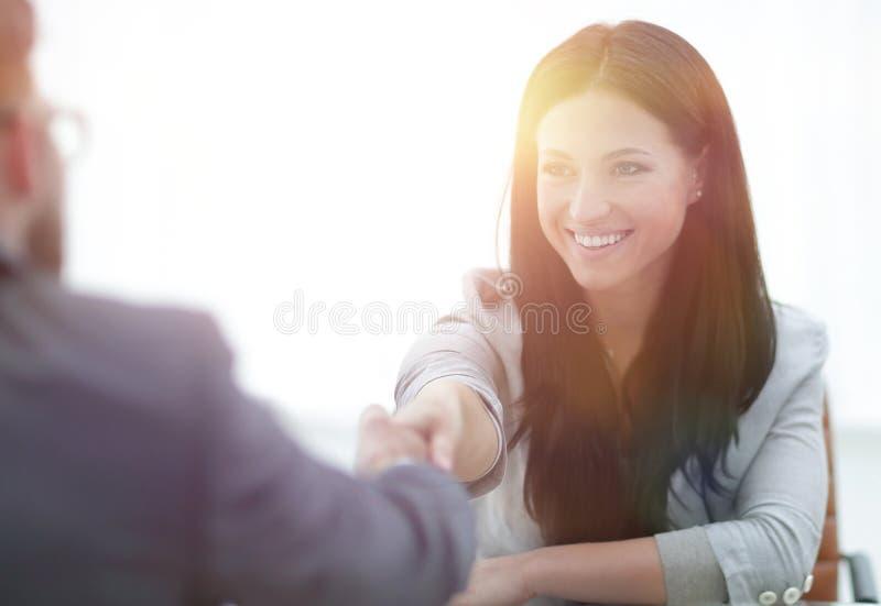 Handdruk jonge bedrijfsvrouw met een partner in het bureau stock afbeelding