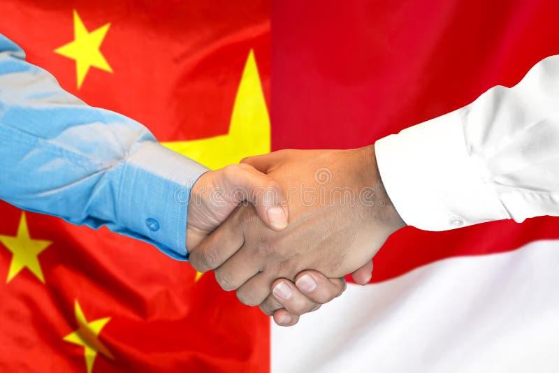 Handdruk op de vlagachtergrond van China en van Monaco royalty-vrije stock afbeelding
