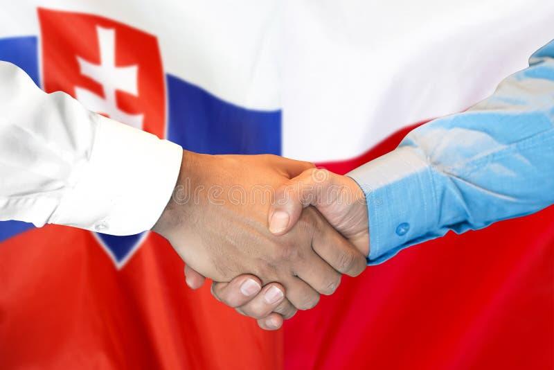 Handdruk op de vlagachtergrond van Slowakije en van Polen stock foto's