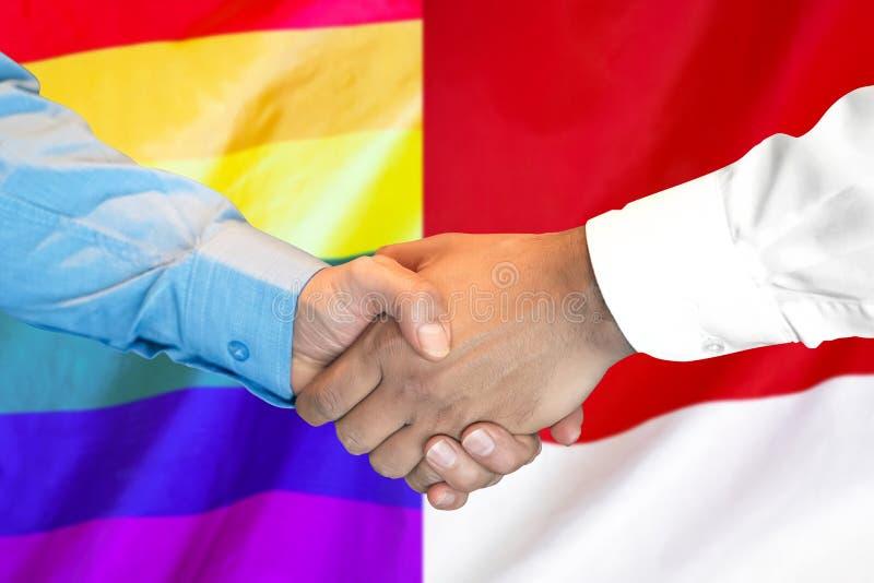 Handdruk op van LGBT de homosexueel en van Monaco vlagachtergrond stock afbeelding