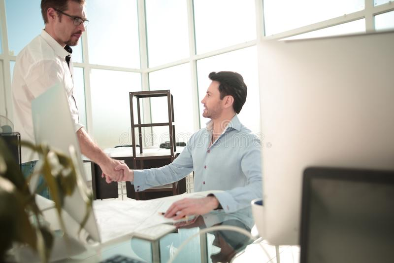 Handdruk tussen agent en klant in een modern bureau royalty-vrije stock foto
