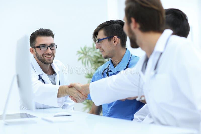 Handdruk tussen de twee artsen tijdens de werkende vergadering stock fotografie