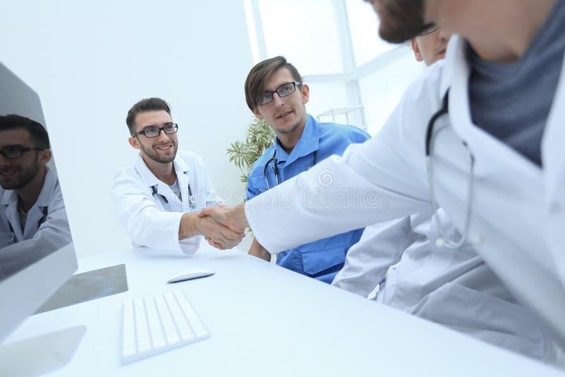 Handdruk tussen de twee artsen tijdens de werkende vergadering stock foto