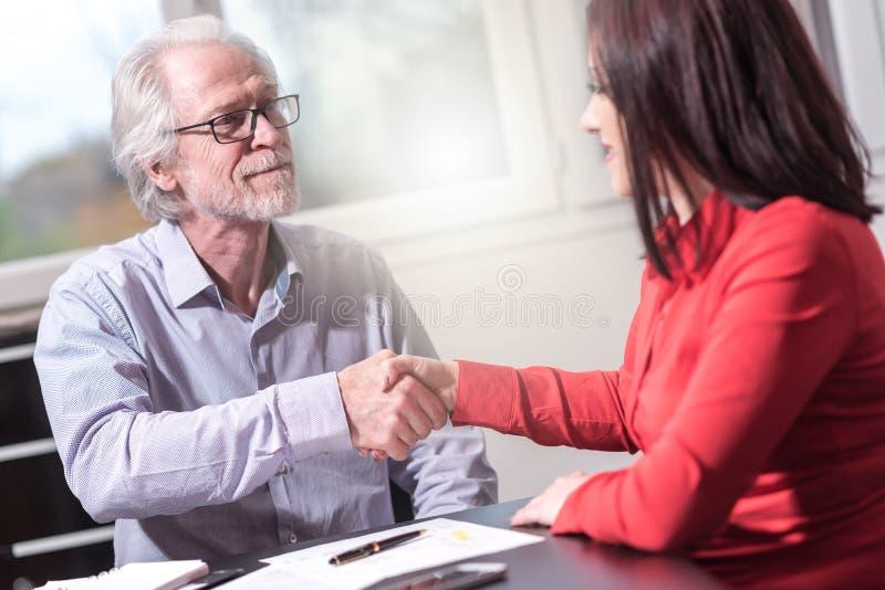 Handdruk tussen vrouw en de mens op kantoor, lichteffect stock afbeelding