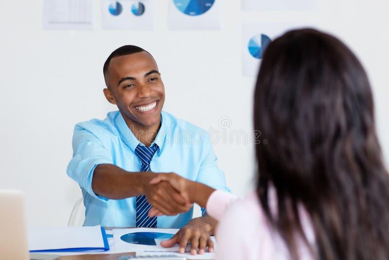 Handdruk van Afrikaans Amerikaans zakenlui na het ondertekenen van contract stock foto