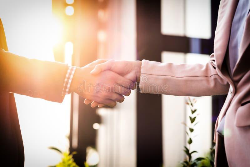 Handdruk van de close-up de vriendschappelijke vergadering tussen bedrijfsvrouw en B stock fotografie