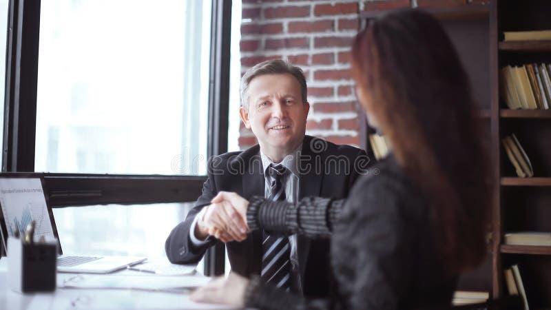 Handdruk van partners die bij hun Bureau zitten royalty-vrije stock foto's