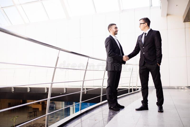 Handdruk van twee bedrijfsmensen die een overeenkomst sluiten op het kantoor stock foto's