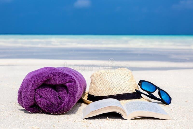 Handduk, hatt, solglasögon och en bok på stranden arkivbilder
