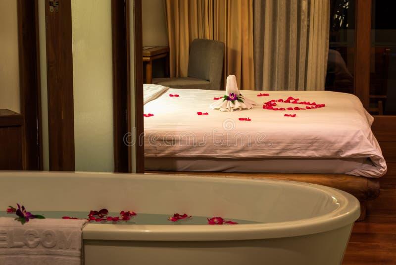 Handdukar, blommor och rött steg kronbladgarneringar på sängen, blommorna och kronbladen i badkaret, begrepp av bröllopsresa royaltyfri foto