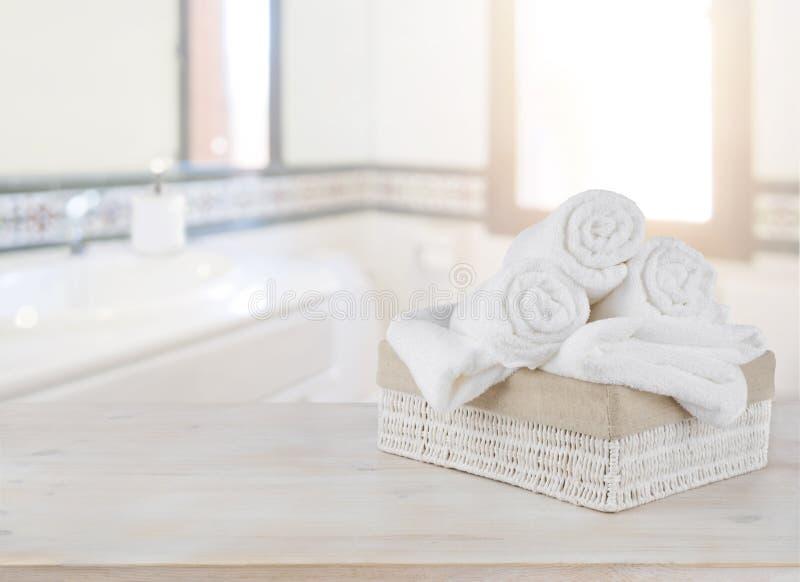 Handdukar i korg på trätabellen över defocused badrumbakgrund royaltyfria bilder