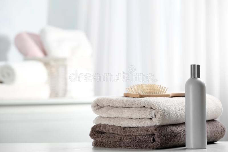 Handdukar med hårborsten och schampo på tabellen royaltyfria foton
