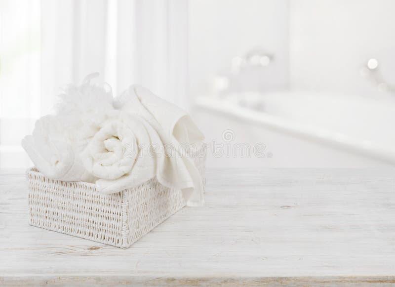 Handdukar och badsvamp i ask över suddig badrumbakgrund royaltyfri fotografi