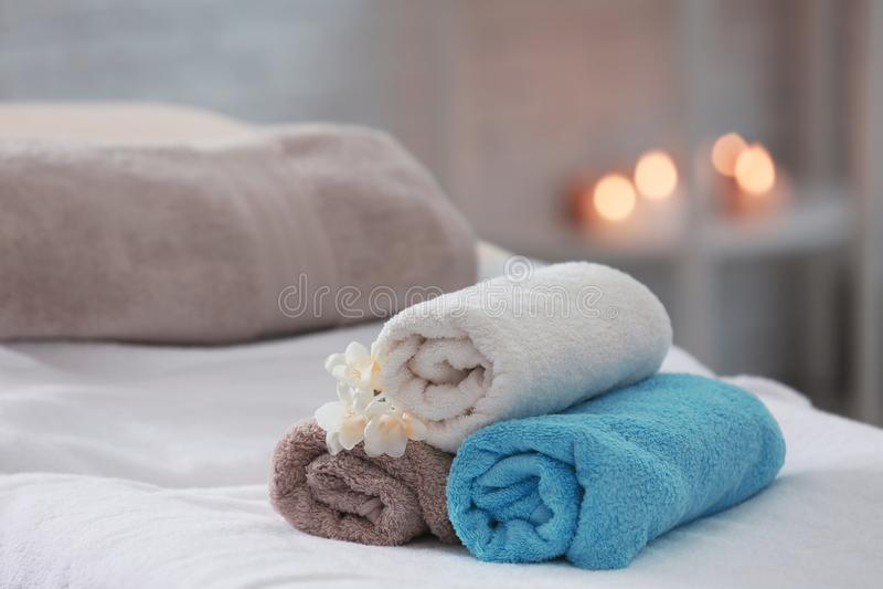 Handdukar och blommor på massagetabellen arkivfoto