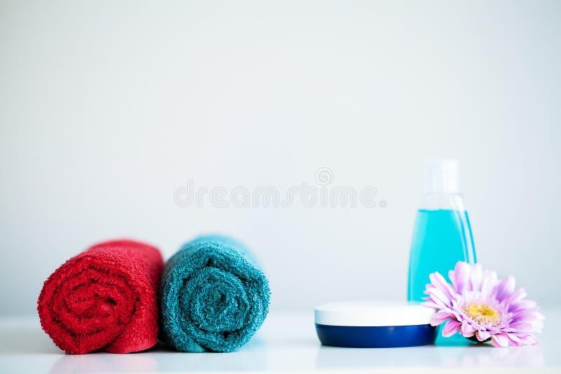 Handdukar och duschen stelnar på den vita tabellen med kopieringsutrymme på badrumbakgrund arkivbild