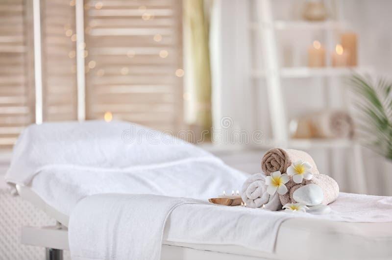 Handdukar och stearinljus på massagetabellen i brunnsortsalong placera avkoppling arkivbilder