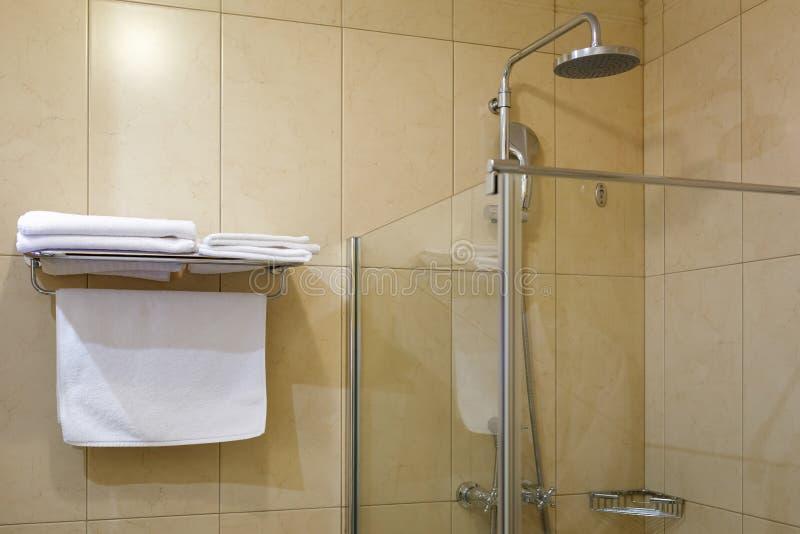 Handdukar på hyllan och den genomskinliga duschenheten i badrummet i hotell fotografering för bildbyråer