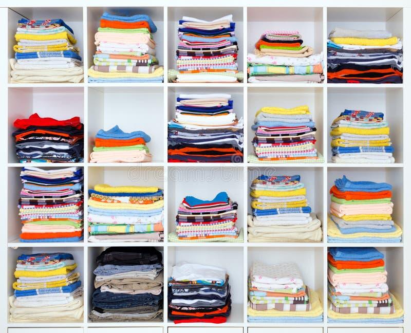 Handdukar, sängark och kläder på hylla royaltyfria bilder