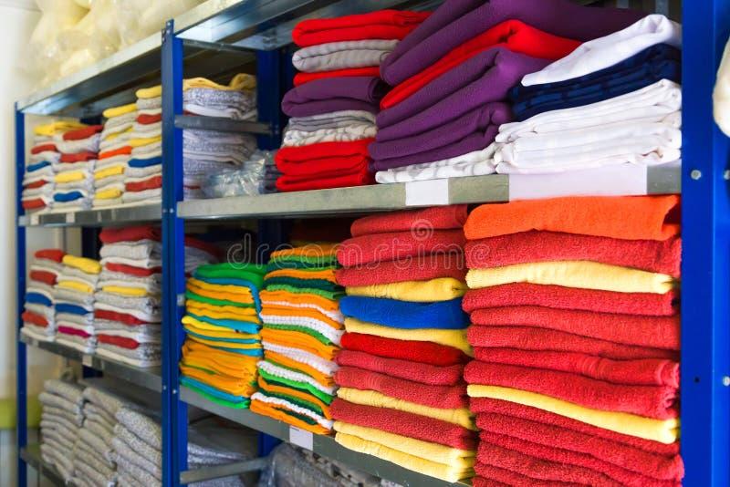 Handdukar, sängark och kläder på hyllan arkivbilder
