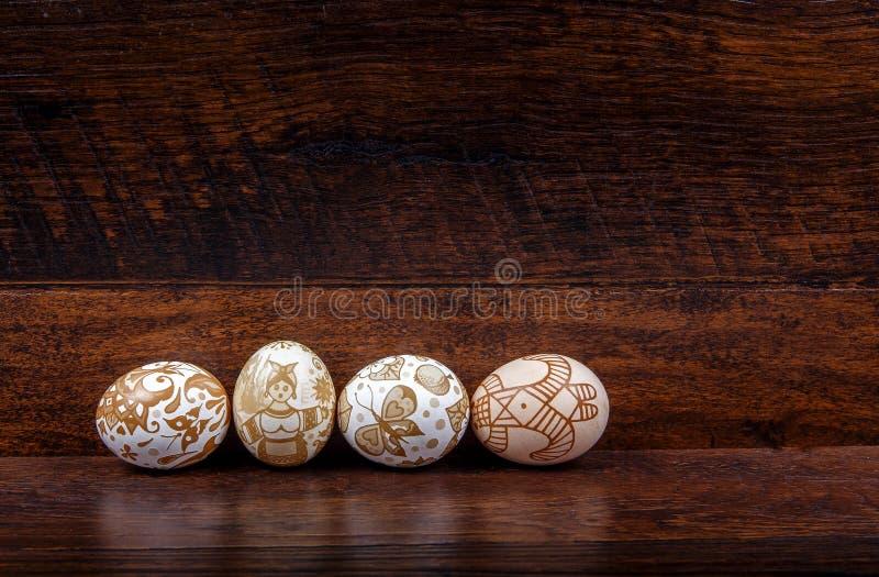 Hande malował Wielkanocnych jajka w gniazdeczku na drewnianym tle zdjęcie royalty free