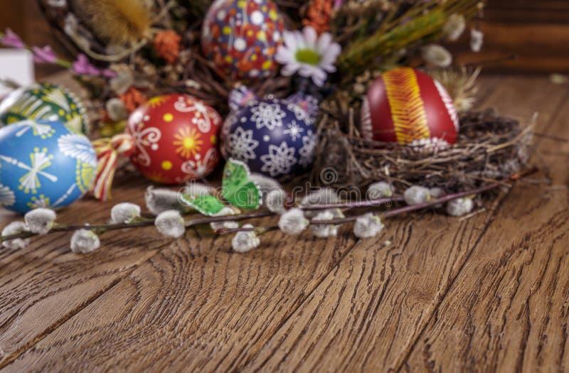 Hande pintó los huevos de Pascua en la jerarquía en fondo de madera fotos de archivo