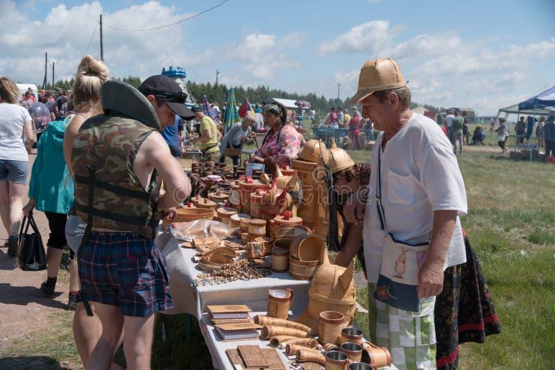 Handel i souvenir från björkskäll på mässan under den etniska festivalen Karatag på kusten av en stor sjö royaltyfri bild