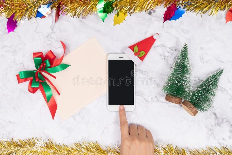 Handel online med säsongsbetonade gåvor under julhelger Knappen för kvinnliga mobiltelefoner dekorerar med plush röd sammet Santa arkivfoton