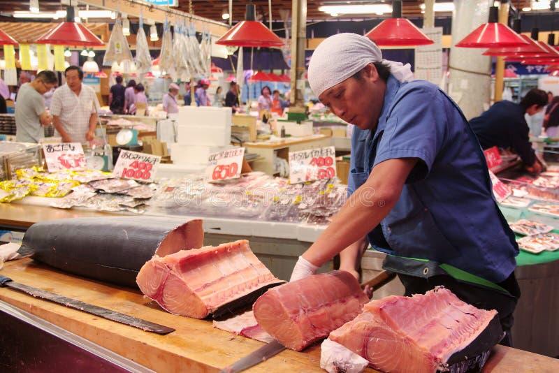 Handelaar knipsel en het filetting zwaardvissenvlees in OMI-Chomarkt Kanazawa Japan stock fotografie