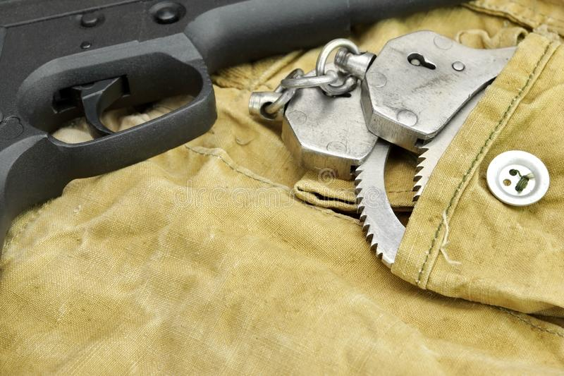 Handeldvapen och handbojor på den red ut ryggsäcken arkivfoto