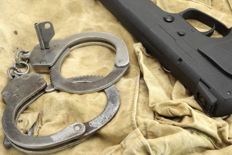 Handeldvapen och handbojor på den red ut ryggsäcken fotografering för bildbyråer