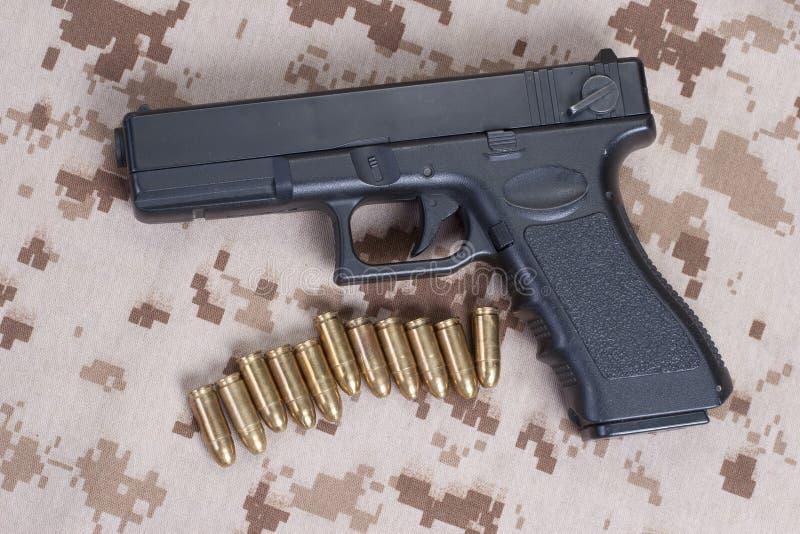 Handeldvapen på kamouflagelikformign arkivfoto