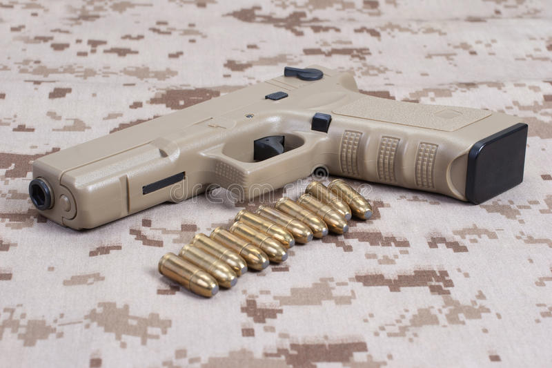 Handeldvapen på kamouflagelikformign arkivfoton