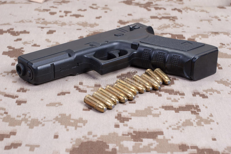 Handeldvapen på kamouflagelikformign royaltyfria bilder