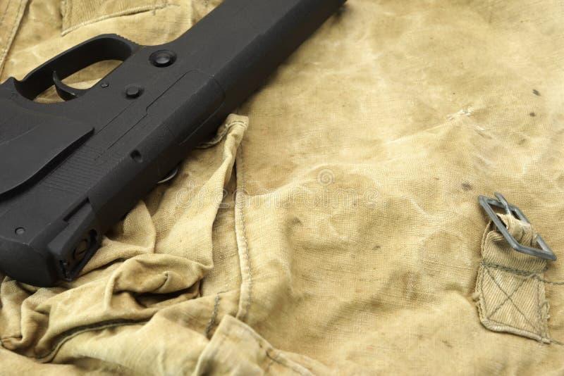 Handeldvapen som ligger över en kamouflagehandväska royaltyfri foto
