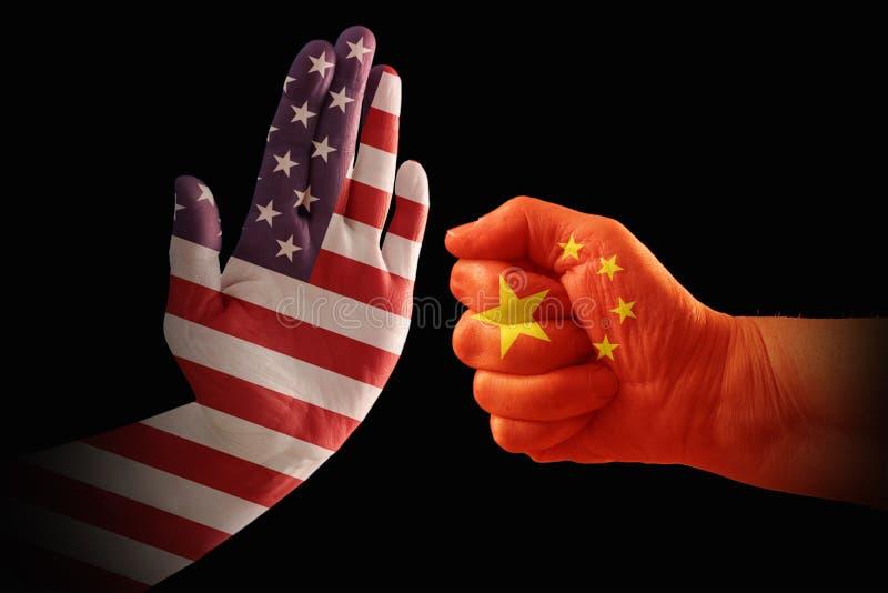 Handelkonflikten, USA flaggan på en stopphand och Kina sjunker på en näve arkivfoto