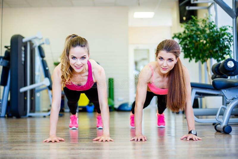 Handeln mit zwei drückt das sportliche Mädchen ups an der Turnhalle lizenzfreies stockfoto
