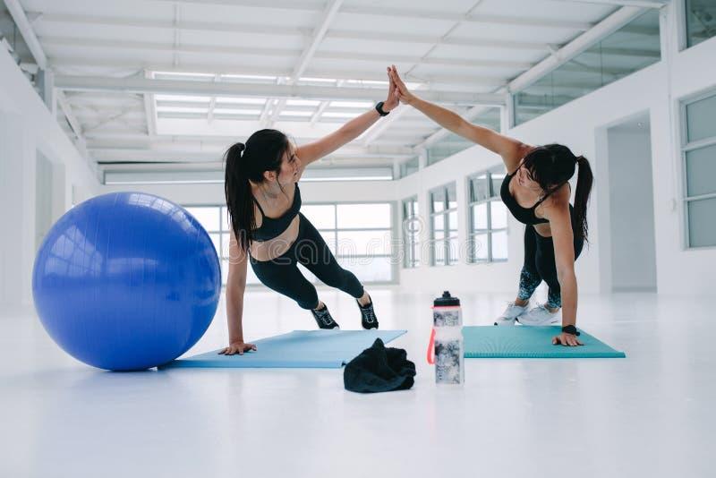 Handeln mit zwei drückt das sportliche Mädchen ups in Turnhalle lizenzfreies stockbild