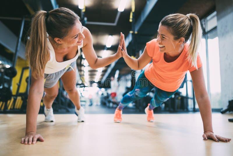 Handeln mit zwei drückt das sportliche Mädchen ups in Turnhalle lizenzfreies stockfoto