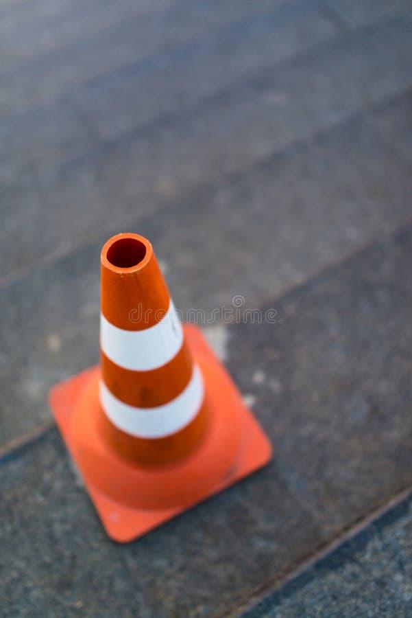 Handeln Sie Kegel, mit den weißen und orange Streifen auf grauem staircace Kopienraum stockfotos