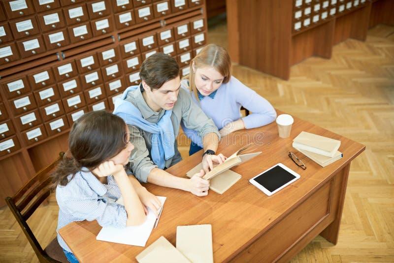 Handeln von Hausarbeit in der Bibliothek lizenzfreies stockbild