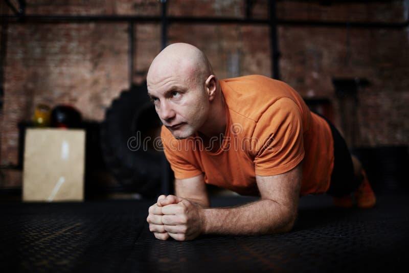 Handeln von Planken-Übung in der Turnhalle lizenzfreie stockfotografie