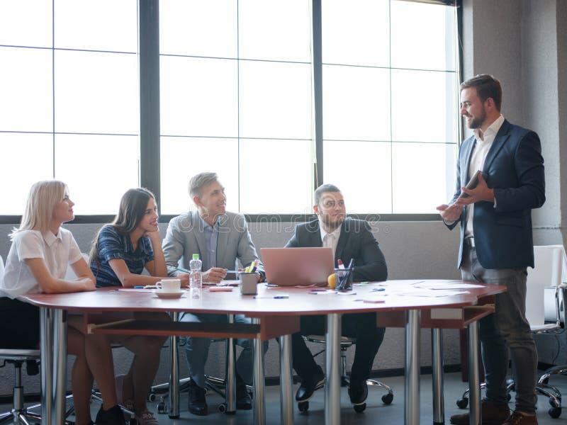 Handelsadviseurs terwijl het werken in een team Een groep jonge werknemers op een vergadering in de ruimte van de bedrijfconferen royalty-vrije stock afbeelding