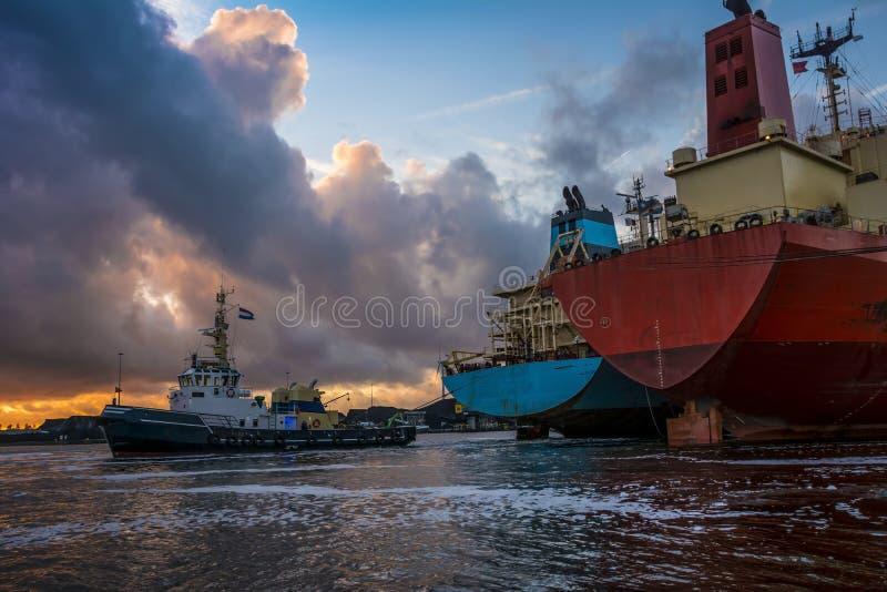 Handelsfartyg är upptagna med att förtöja operationer under solnedgång i port royaltyfria foton