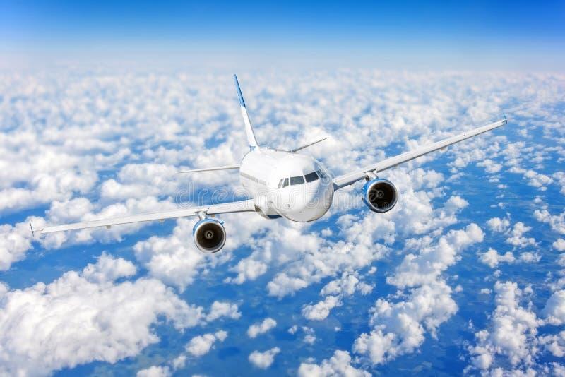 Handelsflugzeug, das über hellen blauen Himmel und weiße Wolken fliegt stockbild