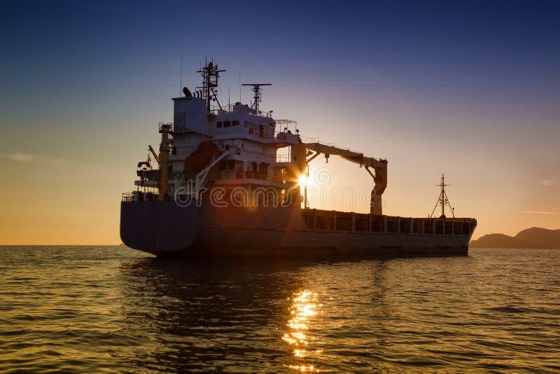 Handelsfrachtschiff bei Sonnenuntergang lizenzfreies stockfoto