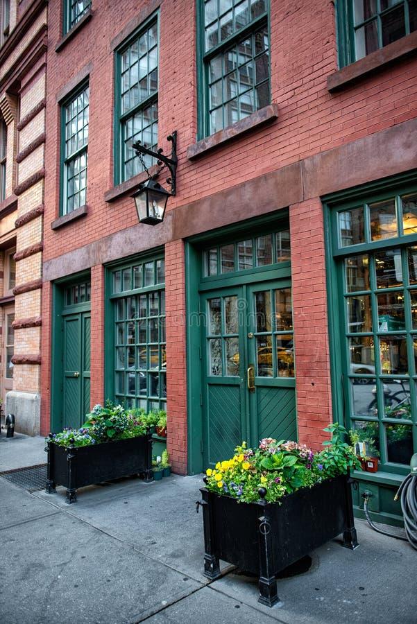 Handelsgebäude der alten Weinleseroten backsteine mit Restaurant innerhalb und grünen Holztüren stockfotos