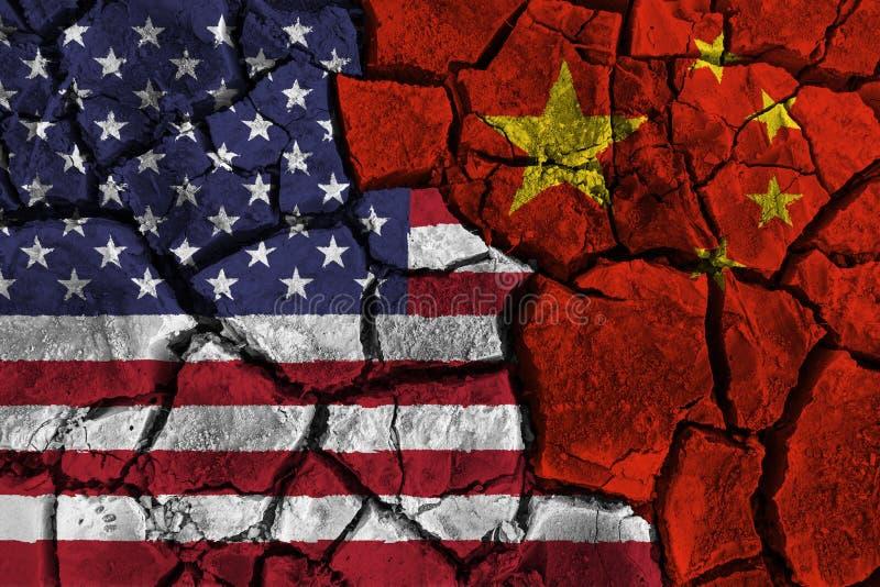 Handelsoorlog tussen de Verenigde Staten van Amerika VERSUS China vlag op gebarsten muurachtergrond Confliction en crisisconcept royalty-vrije stock afbeeldingen