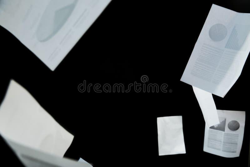 Handelspapieren die onderaan over zwarte achtergrond vallen stock afbeeldingen