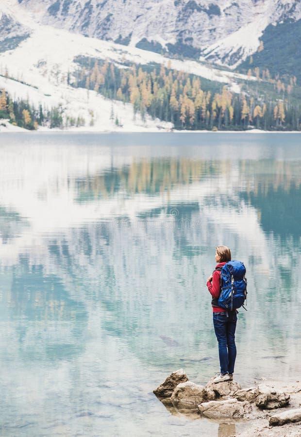 Handelsresande för ung kvinna i fjällängberg som ser på en sjö Lopp, vinter och aktivt livsstilbegrepp royaltyfri bild