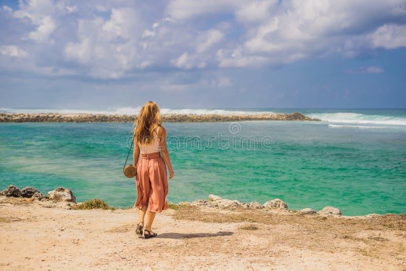 Handelsresande för ung kvinna på att förbluffa den Melasti stranden med turkosvatten, Bali ö Indonesien fotografering för bildbyråer